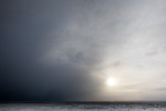 Clouds cover the sun during a passing winter storm in Iceland. by Vermont photographer Monica Donovan