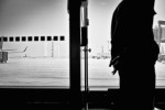 A traveler waits during a layover at Riga Airport in Latvia. by Vermont photographer Monica Donovan