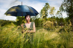 Vermont photographer Monica Donovan shoots a portrait of Rose with an umbrella in a grassy field at Shelburne Farms