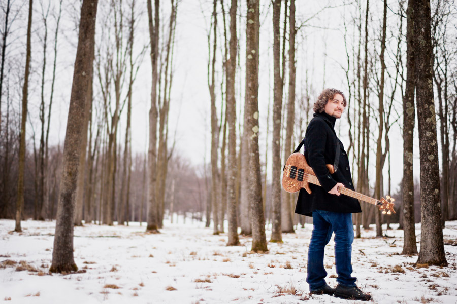 Bassist Aram Bedrosian poses with his guitar in the snowy woods in Shelburne, Vermont.