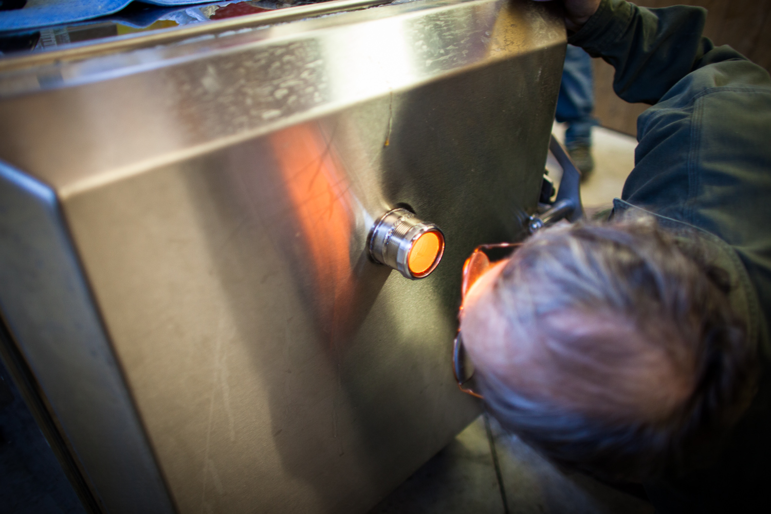 Man peers into a pellet stove while sugaring. By Vermont photographer Monica Donovan