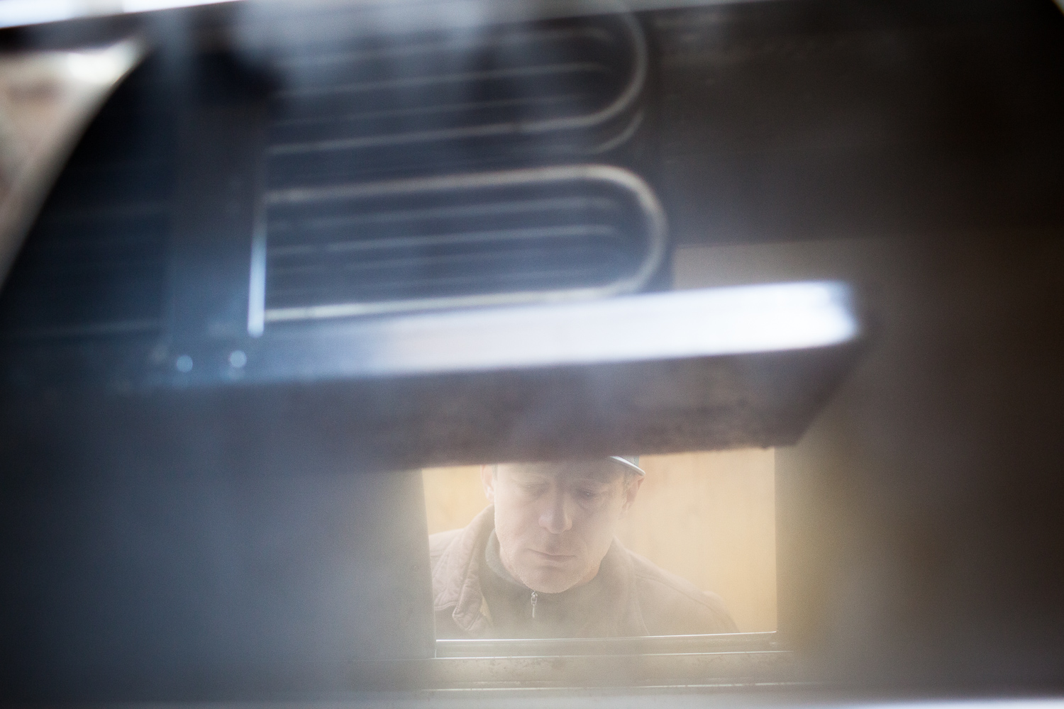 Man peers into an evaporator while sugaring during peak maple syrup season. By Vermont photographer Monica Donovan