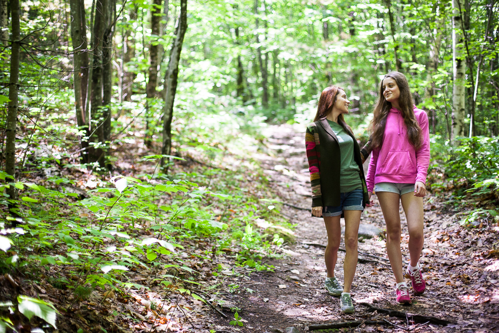Two young women walk in the woods of Maine. by Vermont photographers at Reciprocity Studio, Burlington