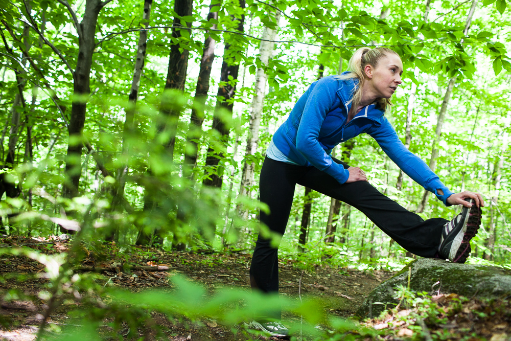 Young woman stretching while running outdoors in forest. by Vermont photographers at Reciprocity Studio, Burlington