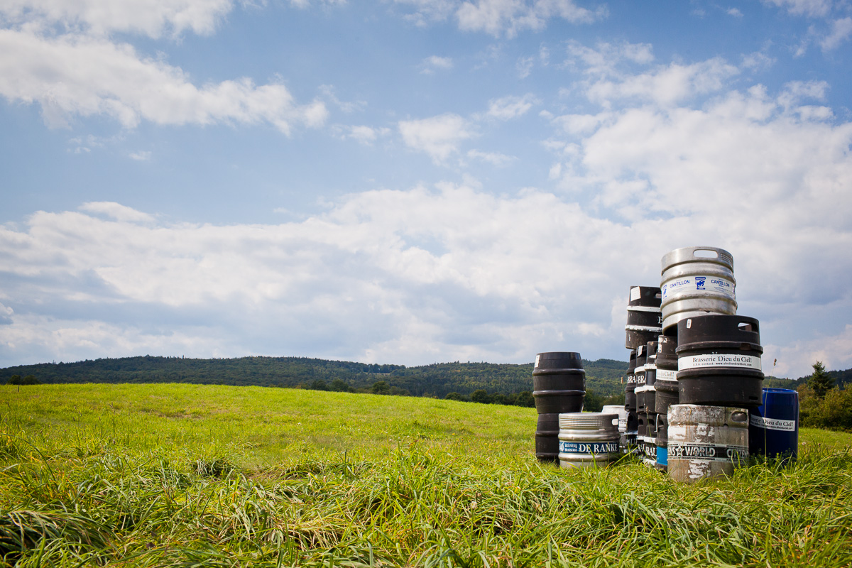 Kegs of beer in a field in Greensboro, Vermont near Hill Farmstead Brewery. by Vermont photographer Monica Donovan.