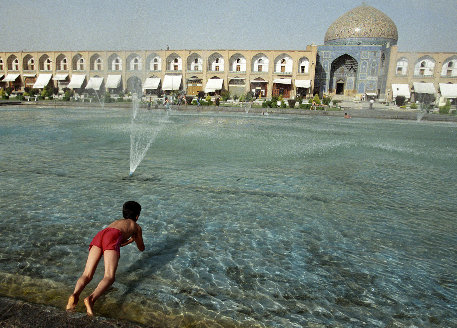 A young boy dives in for a dip in a pool in Iman Khomeini Square in central Esfahan. The Sheik Lotfollah Mosque, built in the 17th century can be seen in the rear.