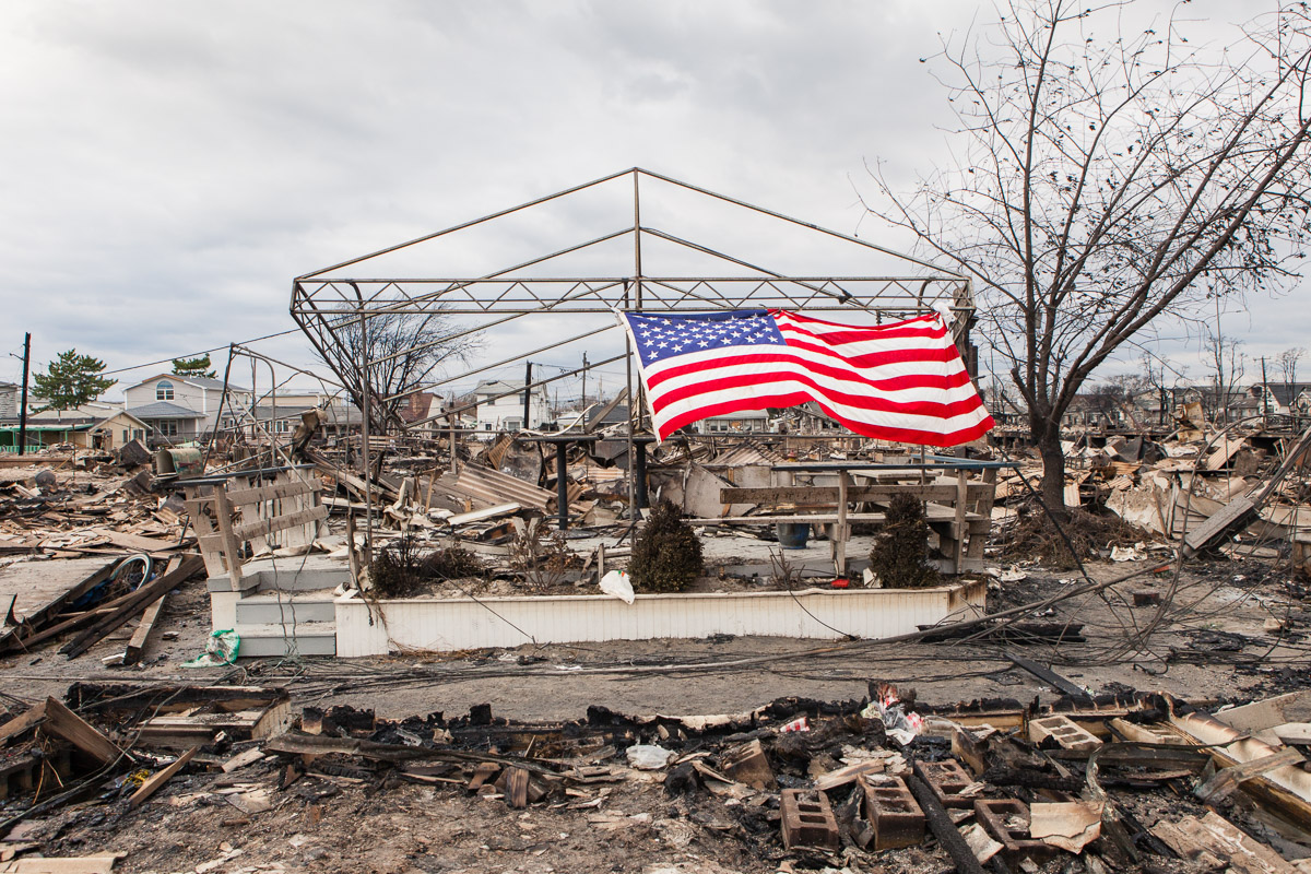 A flag flies amidst the one hundred and eleven homes destroyed by fire in Breezy Point, Queens during Hurricane Sandy. November 1, 2012.