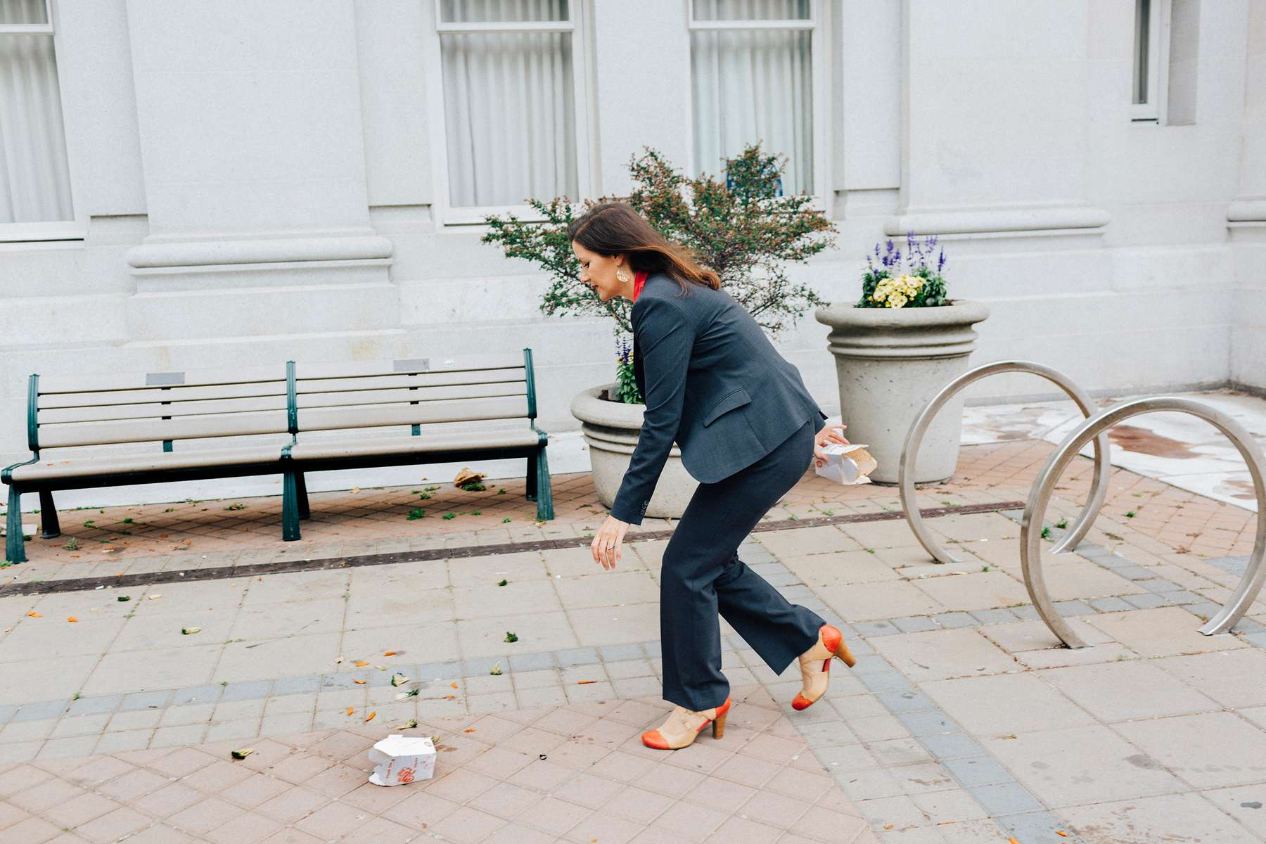 Oakland Mayor Libby Schaaf picks garbage off the sidewalk in front of City Hall on the way to a meeting in downtown Oakland on Wednesday, June 28, 2017 in Oakland, California.