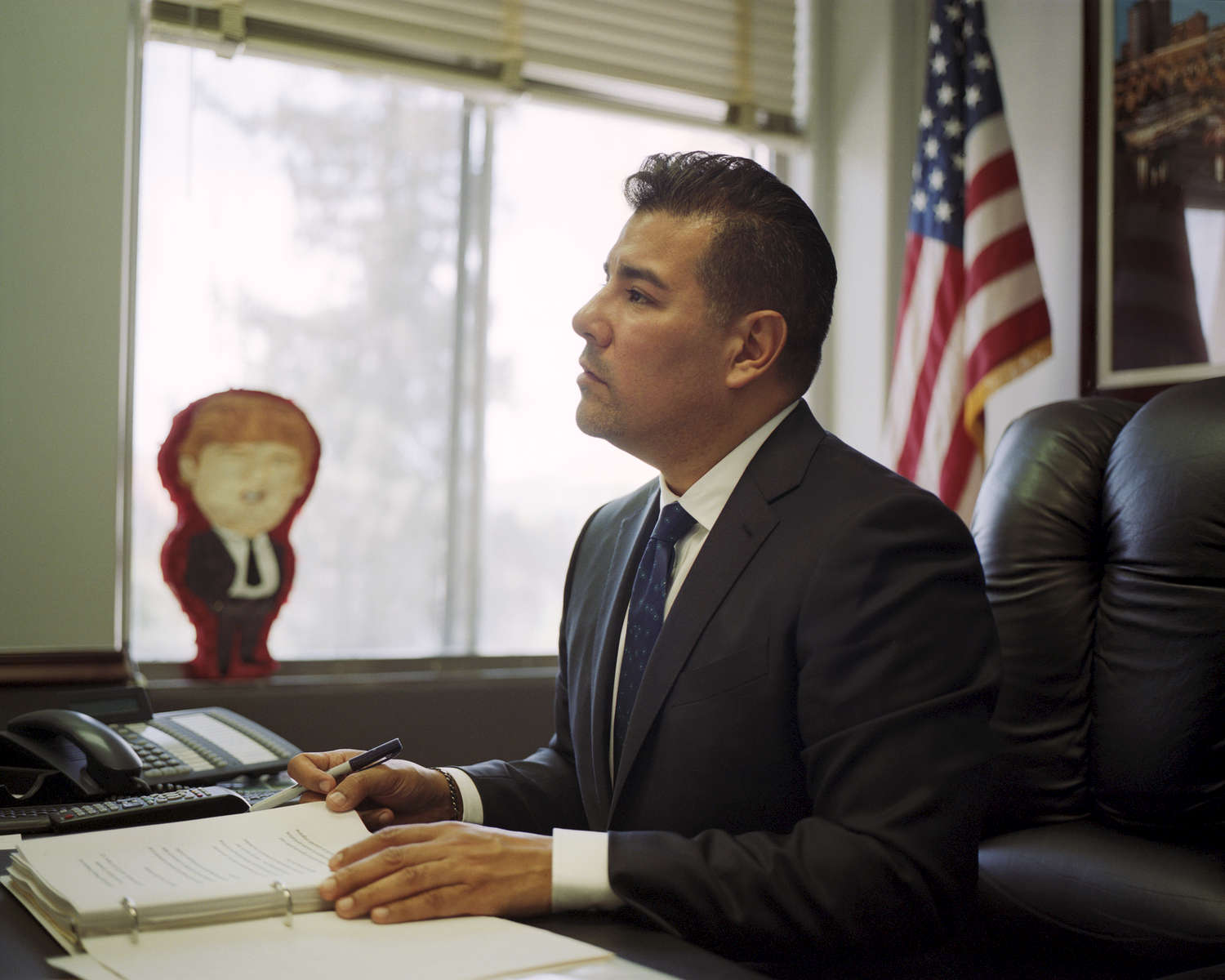 California state senator Ricardo Lara in his office at the Capitol building in Sacramento, CA. Lara wants to do what no one has before him: insure every Californian, even the undocumented. Behind him, on a windowsill, is a Trump piñata from a friend. At the end of the year, he plans to smash it open.