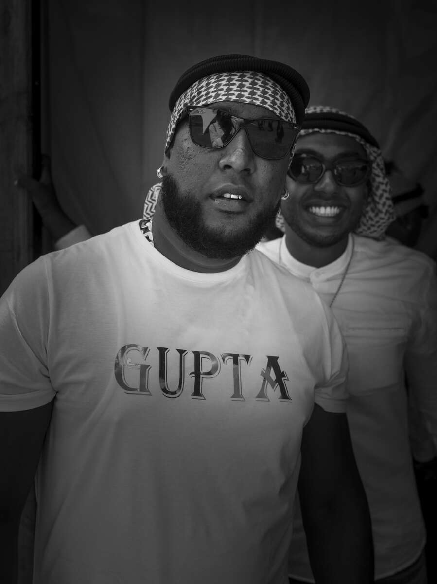 """Cape Town, South Africa: Young man wear the kufiya, golden teeth and jewelleries, dark sunglasses and t-shirts that  feature the name GUPTA  as they attend the The Sun Met. Africa's Richest Horse Race. The Sun Met has announced: 'African Luxury: Visionaries' as the theme for its 2020 annual race day. The Guptas allegedly stole """"hundreds of millions of dollars through illegal deals with the South African government, obfuscated by a shadowy network of shell companies and associates linked to the family"""", the US Treasury said  on the day they imposed sanctions on South Africa's Gupta business family. South Africa is according to TIME the most unequal country on the planet. A surge in Cape Town's murder rate has raised concerns that it could soon challenge for the unenviable title of the world's most dangerous city."""