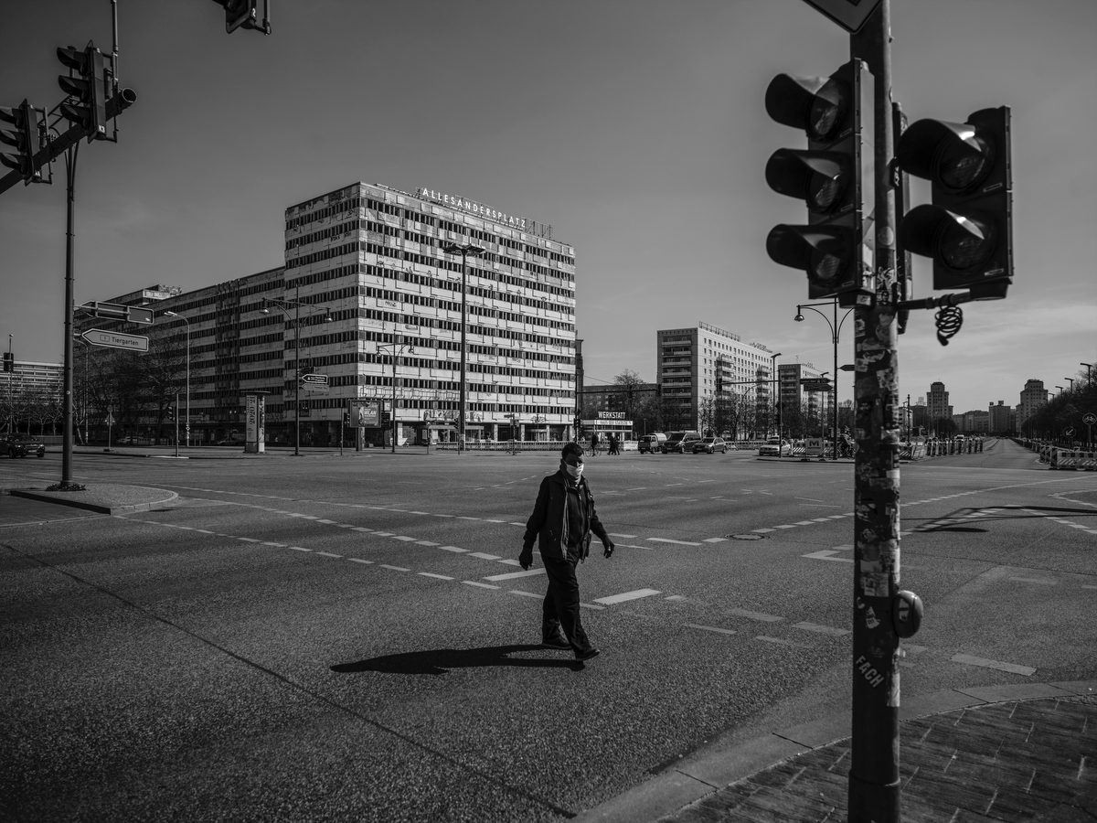 April 05, 2020 - Berlin, Germany: A man wears a mask on Alexander Platz. This crossing counted  about a 100000 cars per day before the shutdown. On top of the high riser in the background artists had mounted a sign that reads: Allesandersplatz. (A play of words which reads:  everything different place). The coronavirus pandemic has hit Germany hard, with more than 100,000 people infected, but the percentage of fatal cases has been remarkably low compared to many neighboring countries. The German Council of Economic Advisers In a special report two weeks ago already  warned that a recession in Europe's powerhouse is inevitable. In a worst case scenario, output will shrink by 5.4%. the Experts predicted.