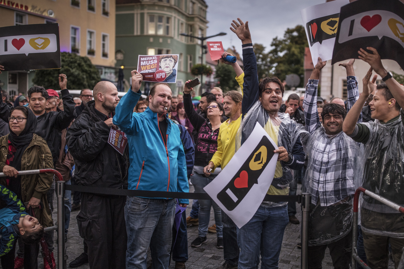 September 06, 2017 - Finsterwalde: Neo Nazi NPD supporters (Center left) stand beside Immigrants (Center right) holding CDU placards as other protesters and hecklers chant 'Merkel muss weg!' ('Merkel must go!') and 'Volksverraeter!' ('Traitor to the people!') while  demonstrating at the edge of an election campaign stop where German Chancellor and Christian Democrat (CDU) Angela Merkel is speaking. Merkel is seeking a fourth term in federal elections scheduled for September 24 and is currently campaigning across Germany.  |