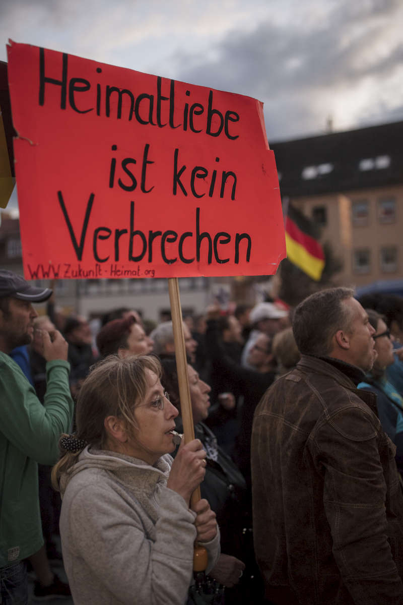 September 06, 2017 - Finsterwalde: A female demonstrator holds a placard that reads: Heimatliebe ist kein Verbrechen (.Homeland love is not a crime) as she joins  Protesters and hecklers chant 'Merkel muss weg!' ('Merkel must go!') and 'Volksverraeter!' ('Traitor to the people!') while  demonstrating at the edge of an election campaign stop where German Chancellor and Christian Democrat (CDU) Angela Merkel is speaking. Merkel is seeking a fourth term in federal elections scheduled for September 24 and is currently campaigning across Germany.  |