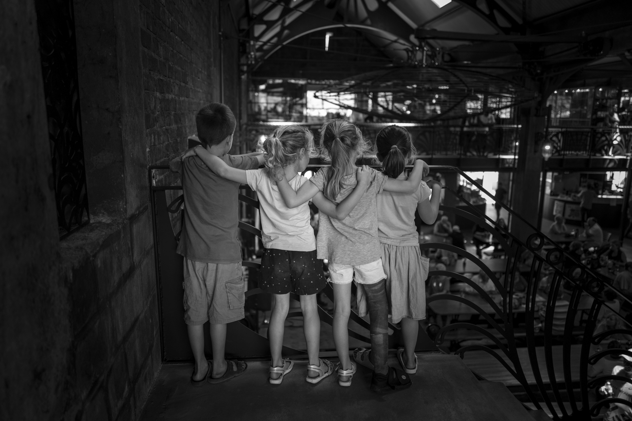Elgin, Western Cape, South Africa: 4 kids link arms to each other as they  watch the hustle and bustle inside  Elgin Railway Market.South Africa is according to TIME the most unequal country on the planet. A surge in Cape Town's murder rate has raised concerns that it could soon challenge for the unenviable title of the world's most dangerous city.
