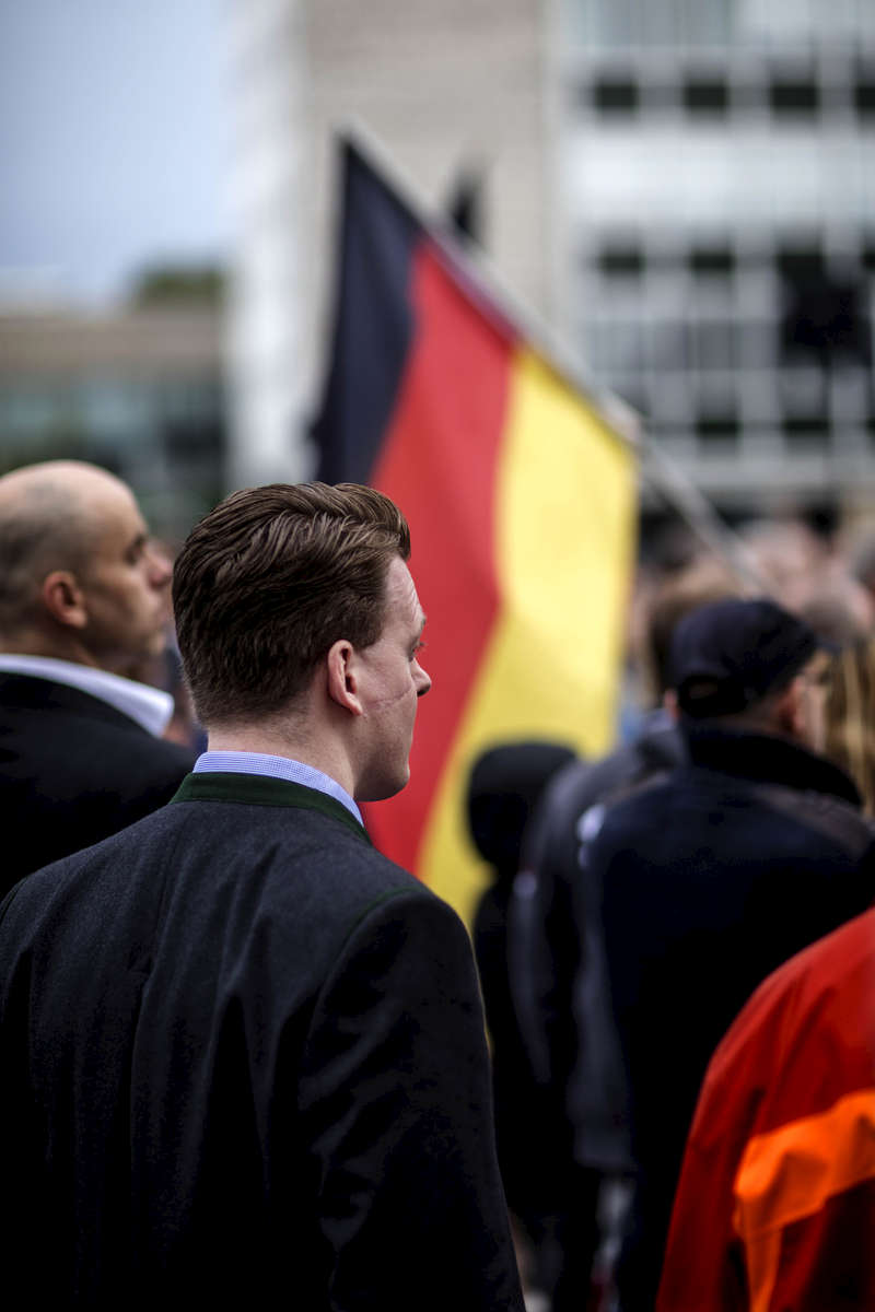 August 12, 2016 -Neubrandenburg, Germany:  A supporter in conservative attire has a gash on his cheek (usually a sign of a member of a duelling fraternity) as he looks on as other supporters  hold AfD placards and German National flags while Bjoern Hoecke, head of the Alternative fuer Deutschland political party (Alternative for Germany, AfD) in Thuringia, agitates a small crowd at an AfD party rally. The anti-immigration party is surging after Germany took in most of the more than 1 million refugees who arrived in the European Union last year. The party's rise is narrowing coalition-building options for Germany's established parties and threatens the status quo nationwide. Polls suggest the AfD will win up to 19% of the votes in this east German state of Mecklenburg-Western Pomerania, where Germanys Chancellor Merkel has her electoral district.