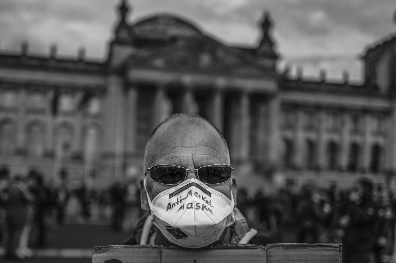 May 16, 2020 - Berlin, Germany:  A man wears a protective mask that reads: Anti Merkel Maske (Anti Merkel mask) and holds a placard that reads: Die die am wenigsten wissen gehorchen am besten (Those who least know obey best) as people gather in front of the Reichstag to protest against lockdown measures and other government policies relating to the novel coronavirus crisis short before police startet to clear the space of demonstrators. Thousands of protesters from a wide spectrum of political creeds, from far left to far right, from the simply disgruntled to conspiracy enthusiasts, are gathering in cities nationwide to protest against government policies and measures many decry as disproportionate and undemocratic. Germany has been easing lockdown measures over recent weeks in an ongoing process.