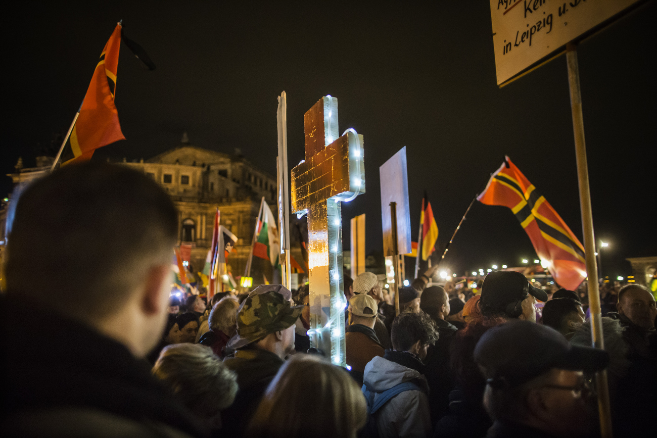 November 16,2015 - Germany, Saxony, Dresden : A demonstrator holds a illuminated cross as he takes part in the demonstration of about 10.000 Supporters of the Pegida movement at their weekly Monday gatherings. Demonstrators shout slogans as: 'Merkel muss weg (Merkel has to go). Pegida is an acronym for 'Patriotische Europaeer Gegen die Islamisierung des Abendlandes,' which translates to 'Patriotic Europeans Against the Islamification of the Occident' and has quickly gained a spreading mass appeal by demanding a more restrictive policy on Germany's acceptance of foreign refugees and asylum seekers. Parts of this  right-wing movement are also against the Euro and the Western liberal style of living in general. The first Pegida march took place in Dresden in October 2014 and has since attracted thousands of participants to its weekly gatherings. But it turned out that even after the Paris attacks last Friday  that left at least more 120 people dead Pegida was not able to show up in larger numbers as in the weeks before the terrorist attacks.