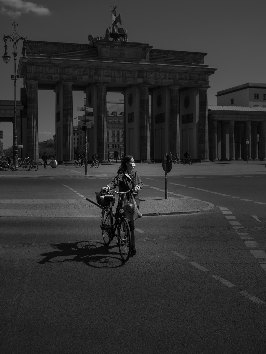 April 17, 2020 - Berlin, Germany:  A woman wears a face mask as she pushes a bike in front of the Brandenburg Gate during the coronavirus pandemic. Usually this is on Friday afternoons a high traffic area. As the rate of new infections nationwide continues to slow, the German government is seeking to establish and implement a roadmap for easing restrictions on public life and the impact  the virus is having on the economy. So far there are over 130,000 cases of confirmed infections of Covid 19 in Germany, over 3,000 people have died and about 57,000 people recovered. (Hermann Bredehorst / Polaris)April 17, 2020 - Berlin, Germany:  A woman wears a face mask as she pushes a bike iin front of the Brandenburg Gate during the coronavirus pandemic. Usually this is on Friday afternoons a high traffic area. As the rate of new infections nationwide continues to slow, the German government is seeking to establish and implement a roadmap for easing restrictions on public life and the impact  the virus is having on the economy. So far there are over 130,000 cases of confirmed infections of Covid 19 in Germany, over 3,000 people have died and about 57,000 people recovered.