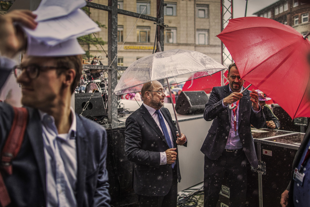 "August 31, 2017 - Kiel: Martin Schulz (C), Social Democrat Party (SPD) leader and SPD party candidate for German Chancellor, holds an umbrella during a heavy rain shower as he stands beside the stage after finishing his speech  to supporters during an election campaign rally under the motto; ""Martin Schulz live"" . Left: Adviser and speechwriter of Martin Schulz, Jonas Hirschnitz covers himself with papers from the rainfall as another adviser protects himself and Schulz on the right. (Hermann Bredehorst / Der Spiegel / Polaris)"