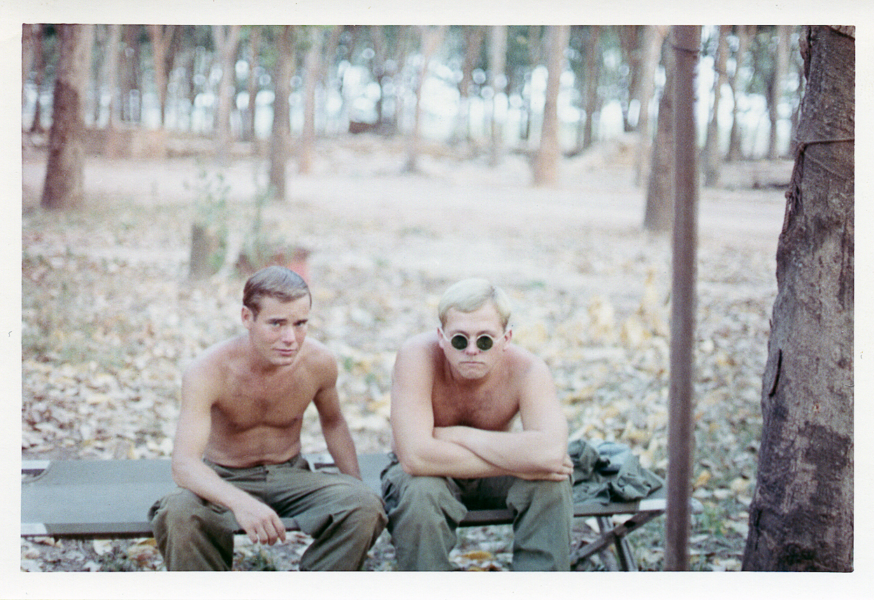 John Phelan and Terry Chaffee sit on a cot just outside of 8 Track in Dau Tieng, South Vietnam, in the Michelin rubber plantaion.