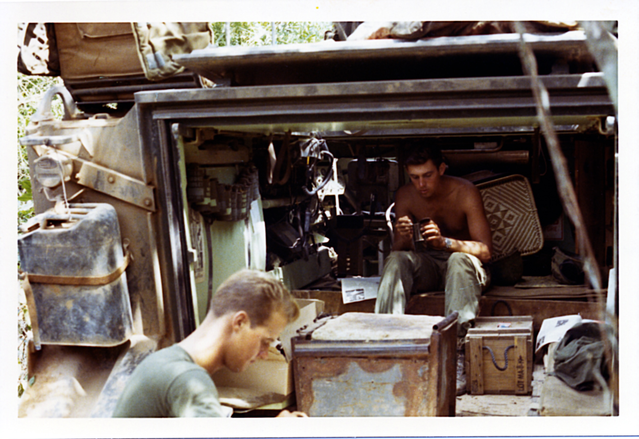 Captain Kirkland L. Alford, A Troop, 3/4 Cav, commander, sits inside the A-6 track while he has a lunch of C-rations. I think that is the A-6 driver in the foreground.