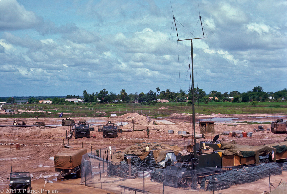 The Command and Communications Center at Fire Support Base Hampton. The southeast edge of Go Dau Ha, South Vietnam, can be seen at the tree line. The monsoon season, 1969.