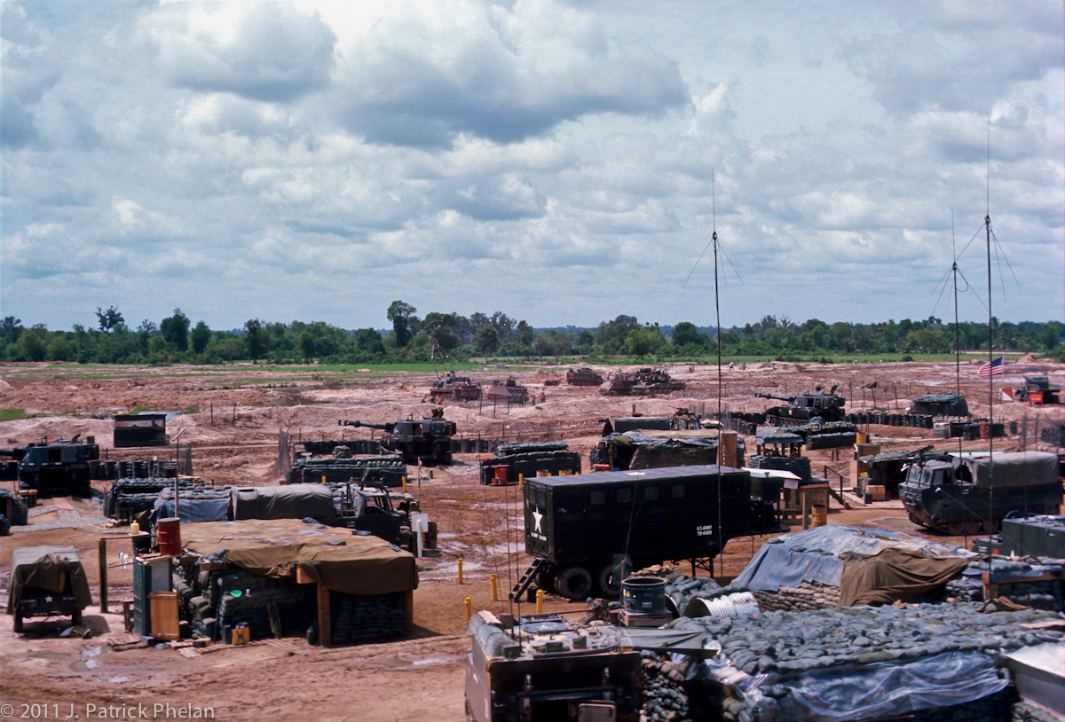 The 3rd of the 13th Field Artillary has the M109 self propelled 155 mm howitzers in position, across the middle of the picure, at FSB Hampton on the southeast edge of Go Dau Ha, South Vietnam. Section 3, the {quote}Base Piece{quote}, is at the far left edge with Section 2 in the center and Section 1 at the right. An M88, with the boom extended, is seen in the distance working with an M113, APC.