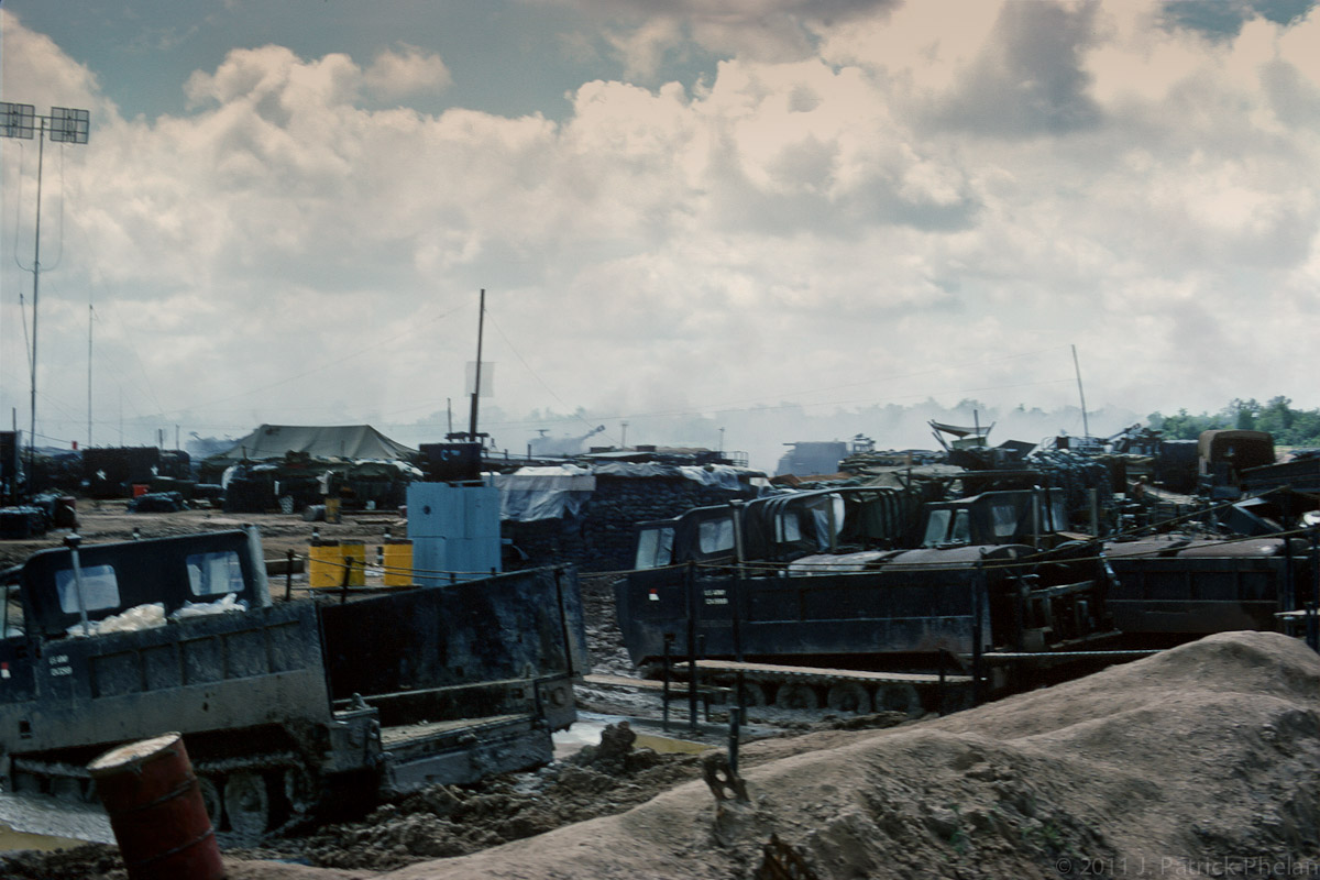 M-548 Cargo Carriers sit in mud during the rainy season along the perimeter of Fire Support Base Hampton on the outskirts of Go Dau Ha, South Vietnam. The 3rd of the 13th Field Artillary M109 self-propelled 155 mm howitzers are seen in the background firing a support mission. 1969.