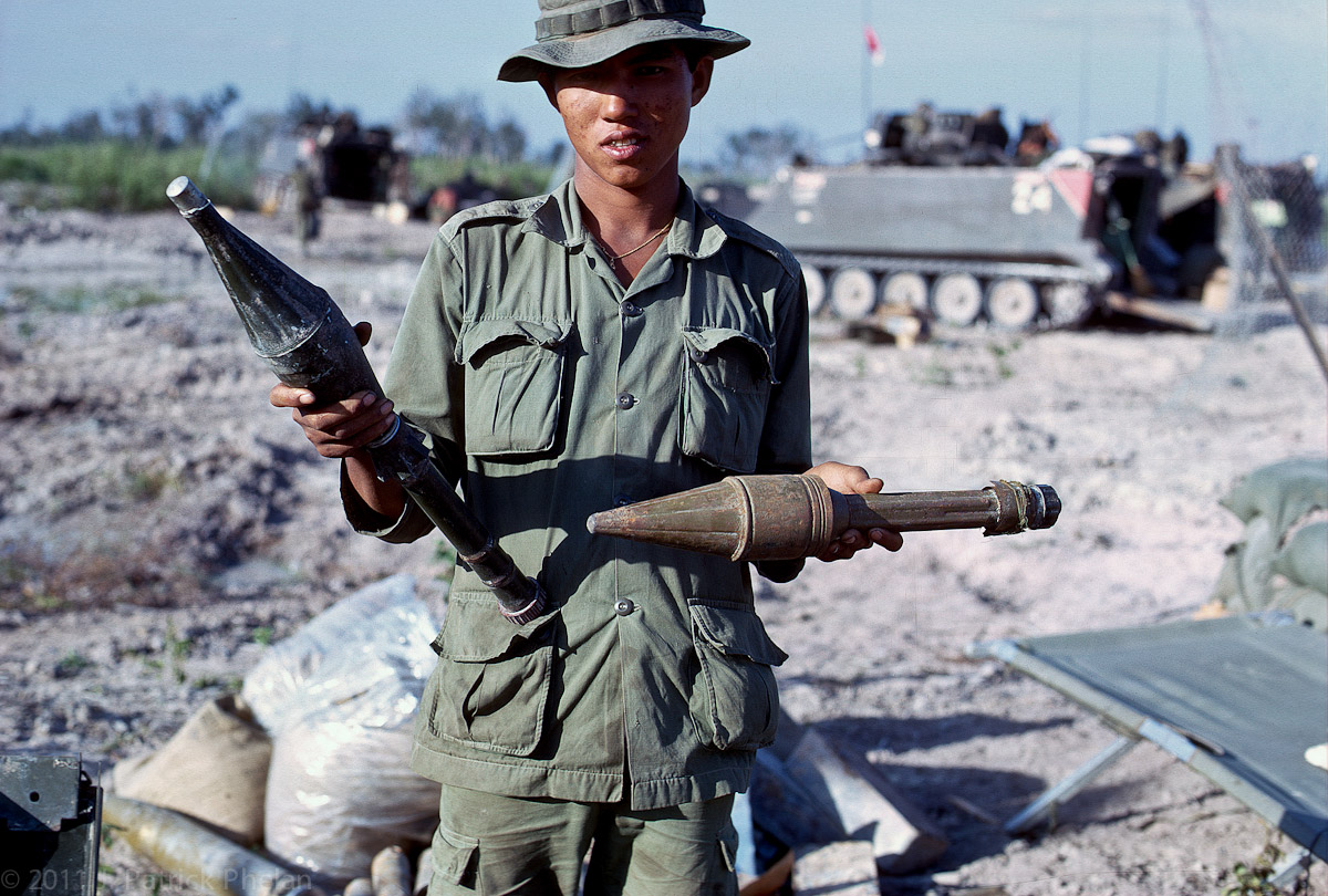 A Chieu Hoi - Open Arms Program (also spelled Chu Hoi), or Kit Carson Scout, holds a Soviet RPG 7 on the left and a Soviet RPG 2 on the right.  The RPGs were a particularly dangerous weapon for the armored cavalry vehicles.