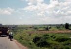 A convoy of personel carriers, tanks, and other military vehicles sits on the MSR with Vietnamese in buses and on bicycles mixed in with the armored vehicles. The bare brown patch of earth at the tree line just to the right of the road is the site of an abandoned fire support base. This site is very close to where the famous photograph, taken by Nick Ut, of 9 year old Phan Thi Kim Phuc is seen running down the road, arms outstreched, after ripping her napalm covered clothes off of herself.