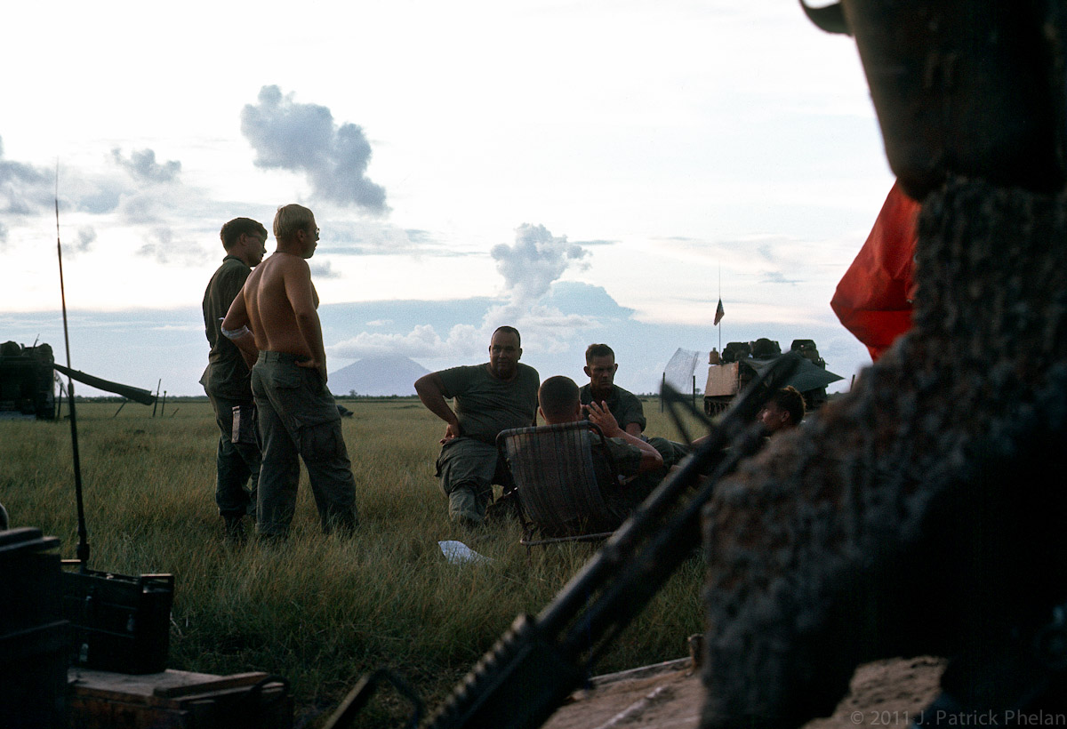 Terry Chaffee on left (w/o shirt), First Sergeant (need name), Capt. Hoag, I believe, seated with back to camera. Need names on others.  An informal meeting to discuss the events of the day and discuss tomorrows plans.  At the right, a corner of the red mail bag hangs on the back of an APC.