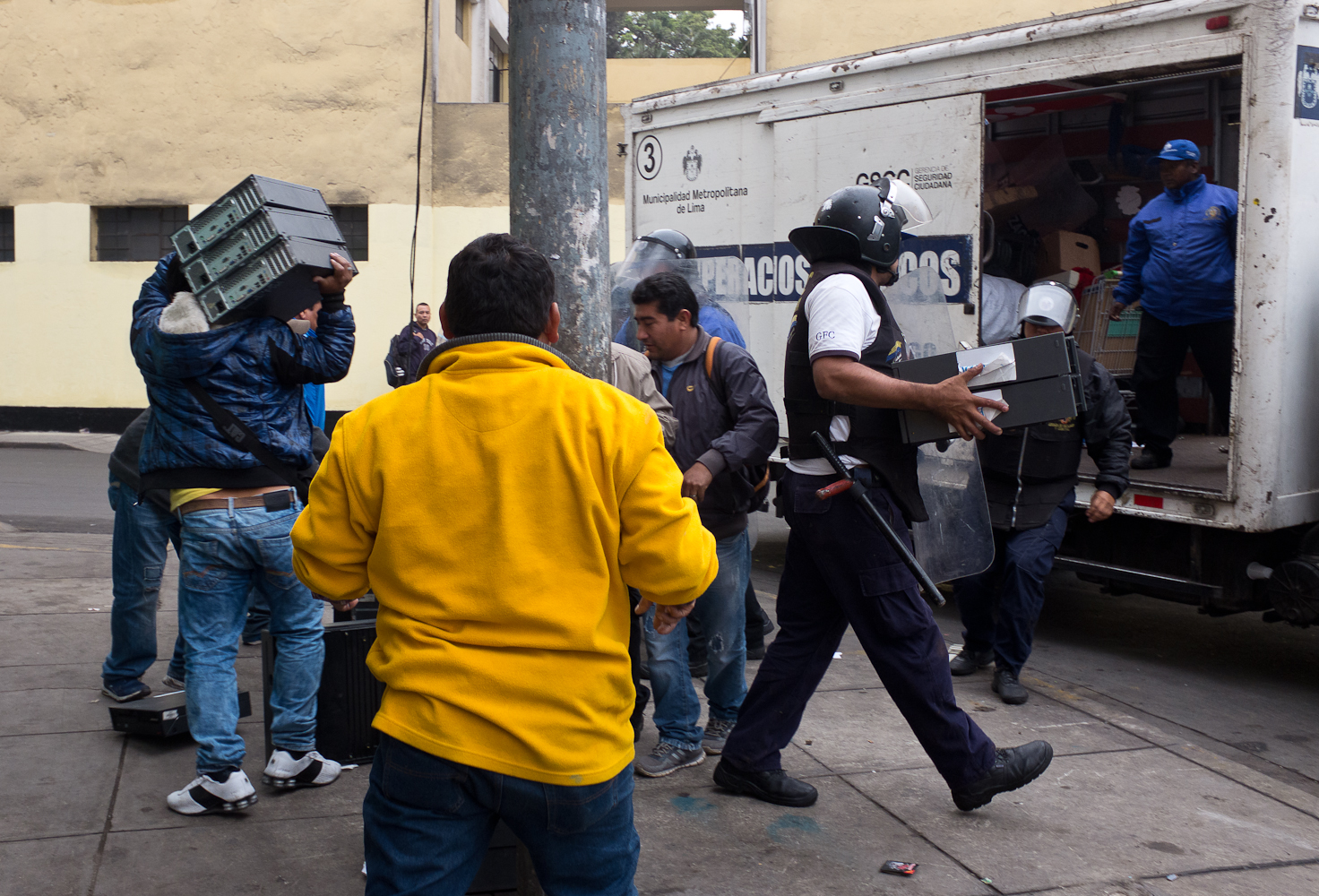 Police conduct a raid on Leticia street, confiscating used PCs for sale that were displayed on the sidewalk seconds earlier. Police periodically raid the informal sector that operates in the open to discourage the practice of informal resale or to confiscate equipment they assume include stolen goods. Police wear masks to hide their identity for fear of personal retaliation if people recognize them.