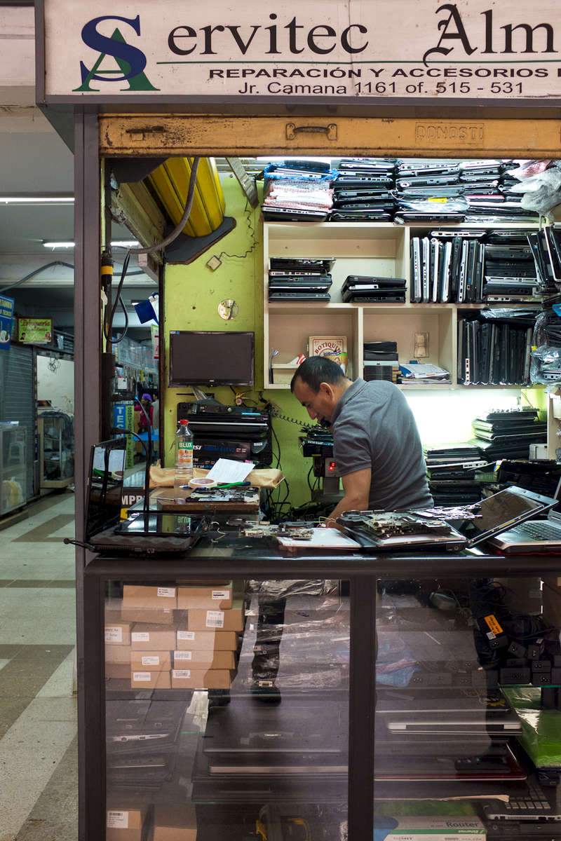 An electronics repair shopowner in central Lima, in an indoor mall which specializes in electronics refurbishment and resale.