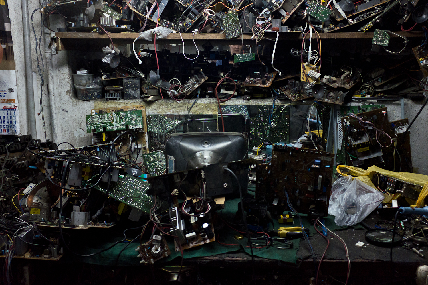 In Victor Arevalo's shop, it costs about $8 USD to repair a CRT TV. Repair shops purchase or hoard components from used TVs to fix their customers' products. Used parts are no longer available from the original manufacturer. Images such as these are often used to demonstrate the environmental hazards of electronic scrap flows, but closer inspection confirms that the space is, well, just messy. Though the components are strewn everywhere, they are simply inventory.