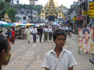 Local boy stands amidst people running errands outside the Shwedagon Pagoda.