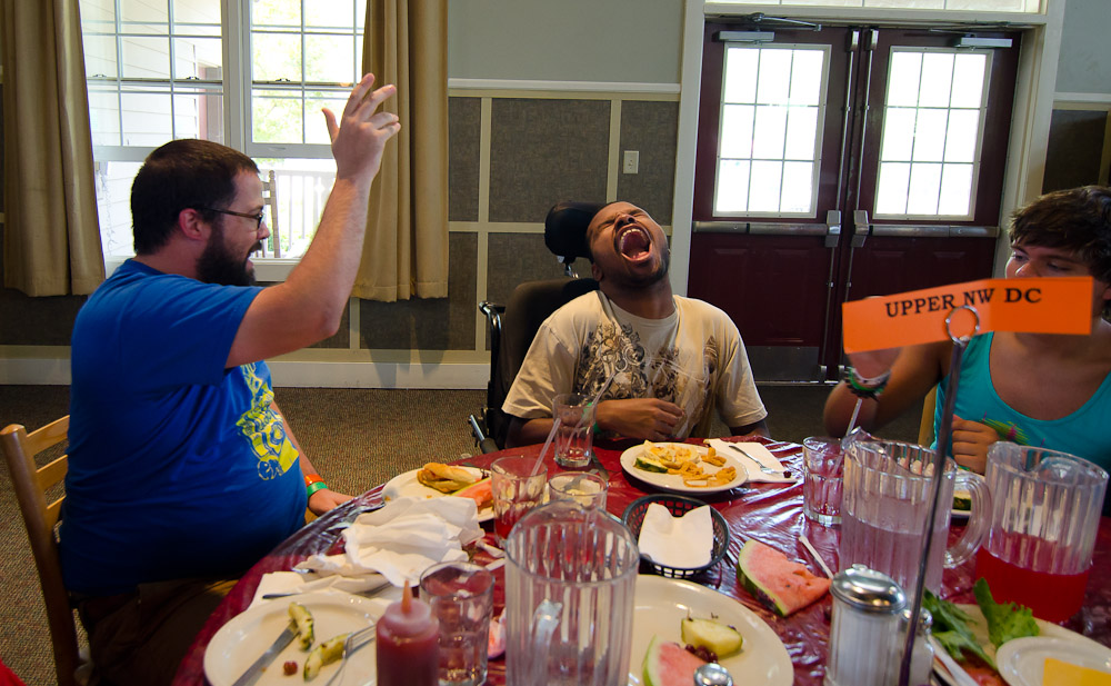 A camper attempts to catch a grape in his mouth as food flies across the table.