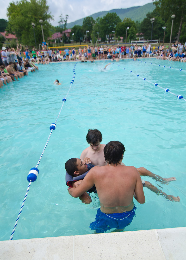 Two leaders assist a camper during the water relay race.