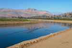 A reservoir, intended only for crop irrigation, winds its way through fruit groves. The pristine water is sourced from the Sierra Nevada mountains. Such water is not accessible to local communities for drinking water.