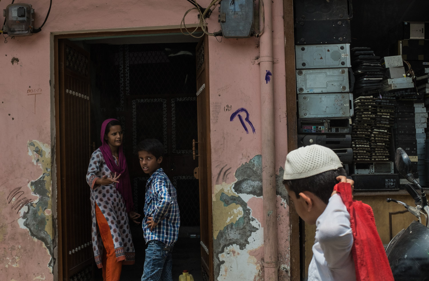 Mustafabad. Children interacting in front of their home, which also serves as a storage facility and  electronics dismantling workspace.