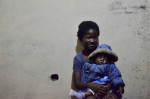 Millie, an orphan at St. Luke's who is cared for by Pastor Joshua and Abigael holds their adopted son, Bridge. Seven months earlier, Abigael found him, an abandoned newborn, at the foot of a bridge and named him accordingly.