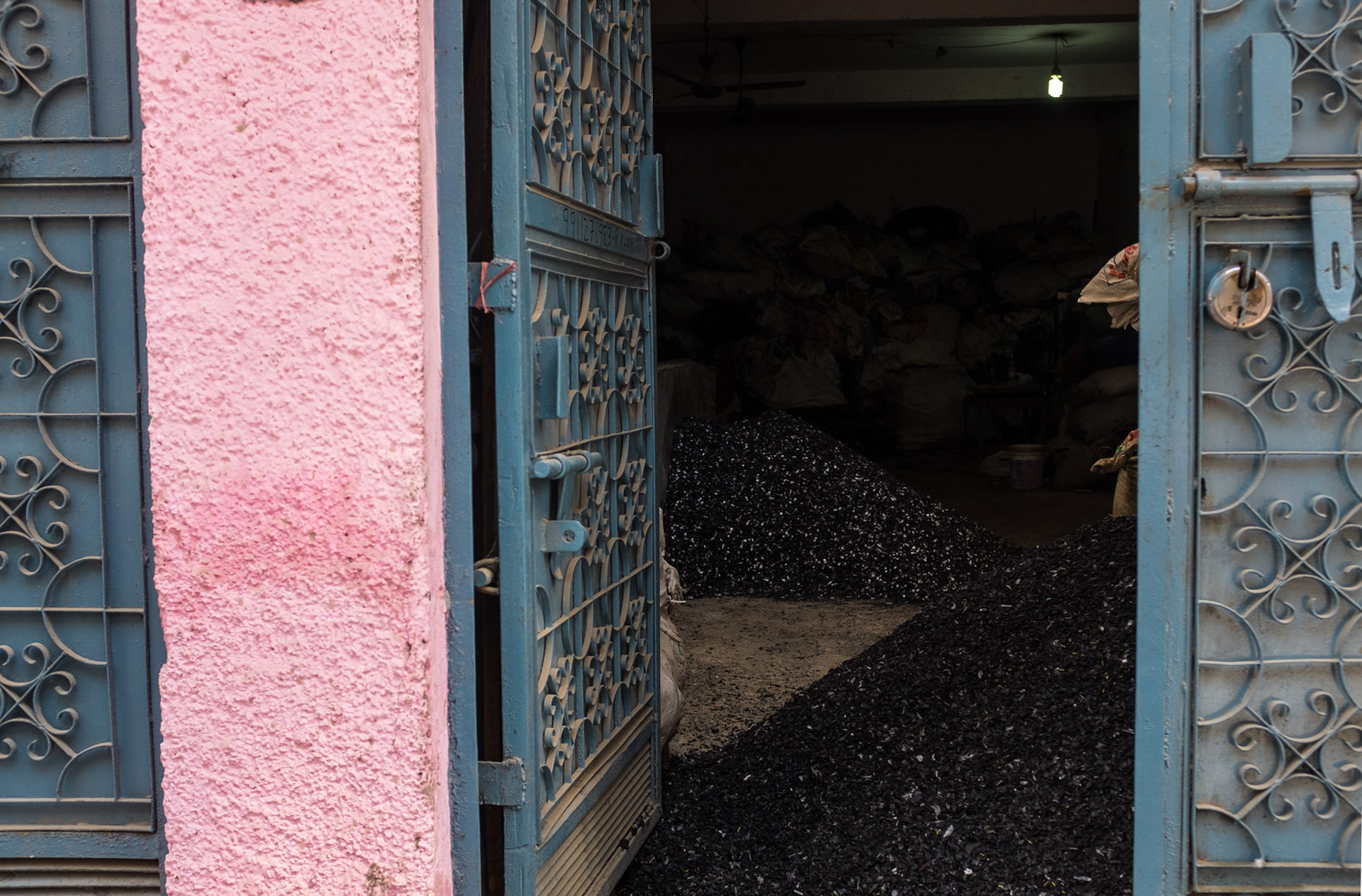 An unassuming residential building contains a workspace where plastics and metals are sorted in Mustafabad, a slum outside New Delhi.