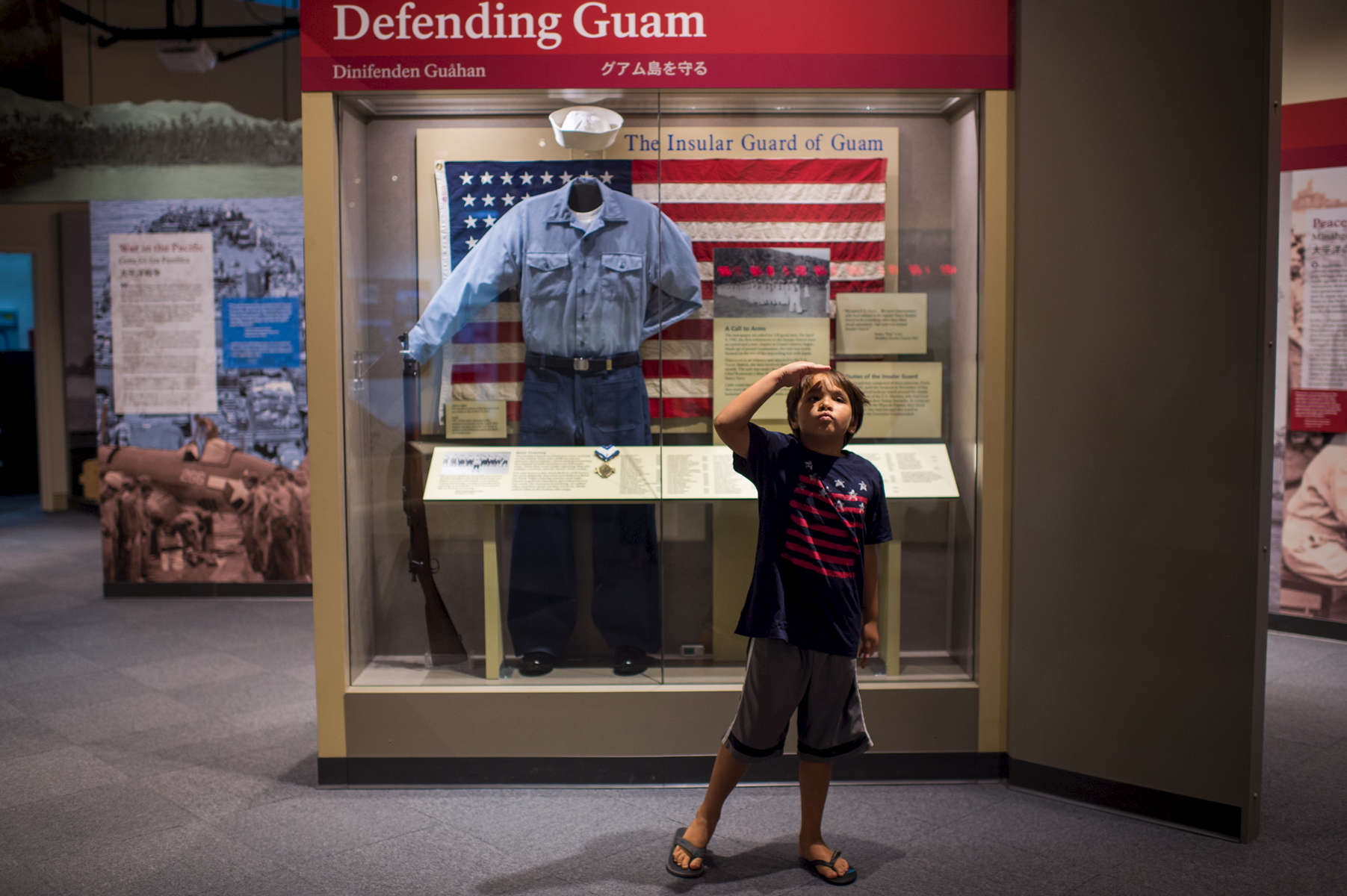 Gianni Que, 7, salutes his mother Genesa while one a visit to the War in the Pacific National Historical Park museum on Guam. (Aug 10, 2017)Photo by Nancy Borowick