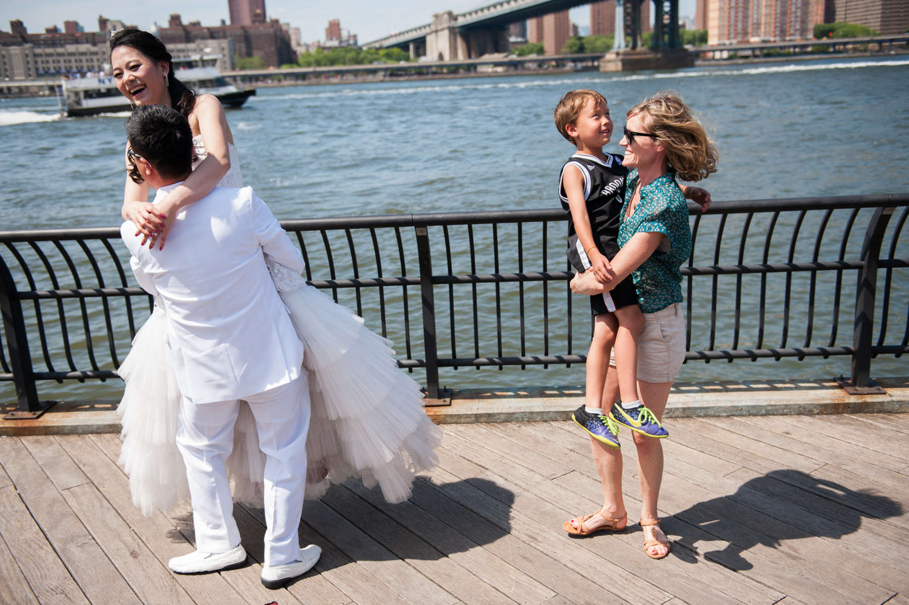 It's not unusual to see co-founder of The Knot photo-bombing wedding photographs in her Dumbo neighborhood. Shes pictured here, twirling her son Dumbo, 6, next to bride Tracy Lin and husband-to-be Dezhi Yang. (June 8, 2014)Photo by Nancy Borowick