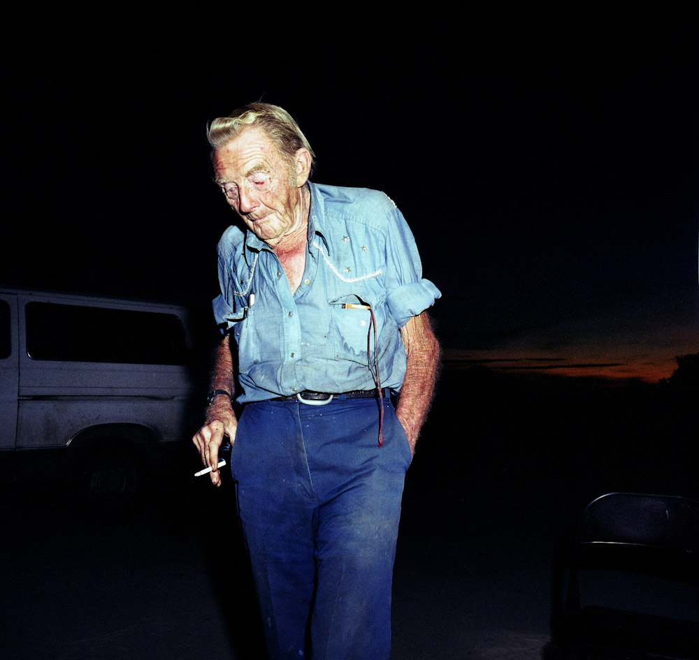 Red smokes a cigarette after sunset, Slab City.