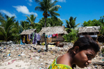 A girl walks past the camera on the foreshore of the over populated Bairiki Village. A lack of infrastructure means that sewage and garbage are disposed on the beach.