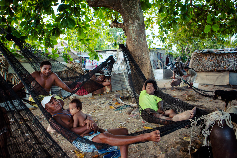 Men relax during the heat of the day on hammocks. People are most active around dawn and dusk when the temperature cools. Bairiki Village, Tarawa Island, Kiribati.