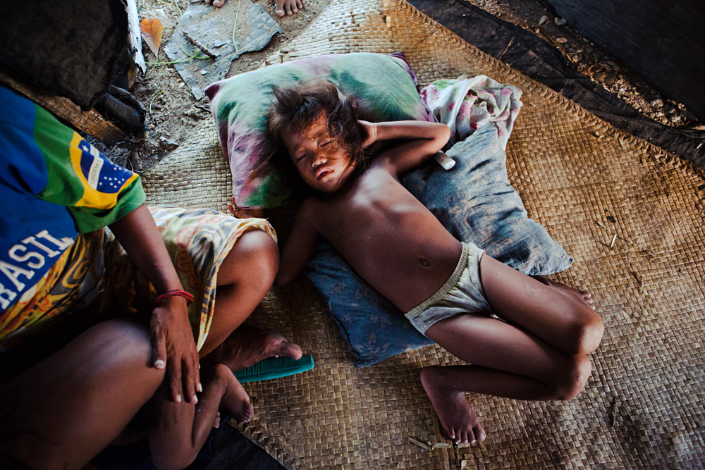 bairiki Village. Ocean Side, Tarawa. A high density slum area. A baby naps on a wovan palm mat in her home.