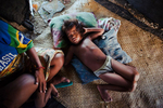 bairiki Village. Ocean Side, Tarawa. A high density slum area. A baby naps on a wovan palm mat in her home.