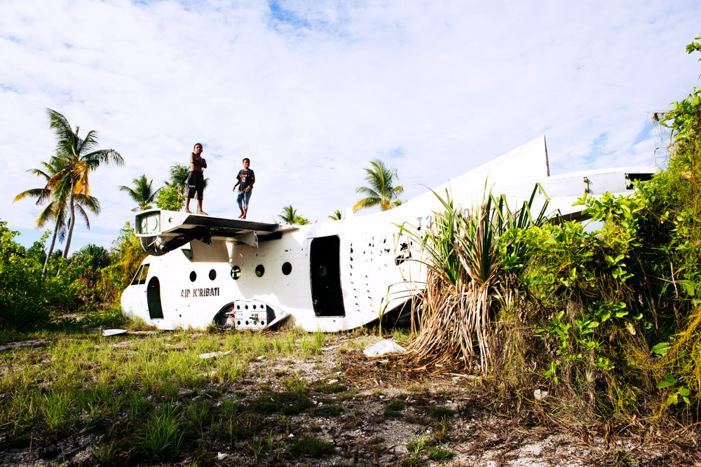 Children play on an abandoned aircraft at the Tarawa Airport, Kiribati.
