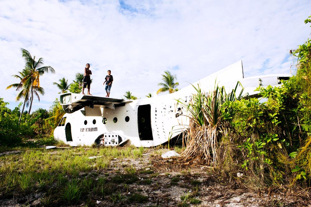 Children play on an abandoned aircraft at the Tarawa Airport, Kiribati.